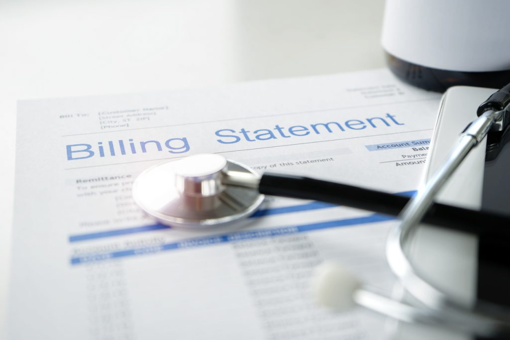 Health care billing statement with stethoscope, bottle of medicine for doctor's work in medical center stone background.