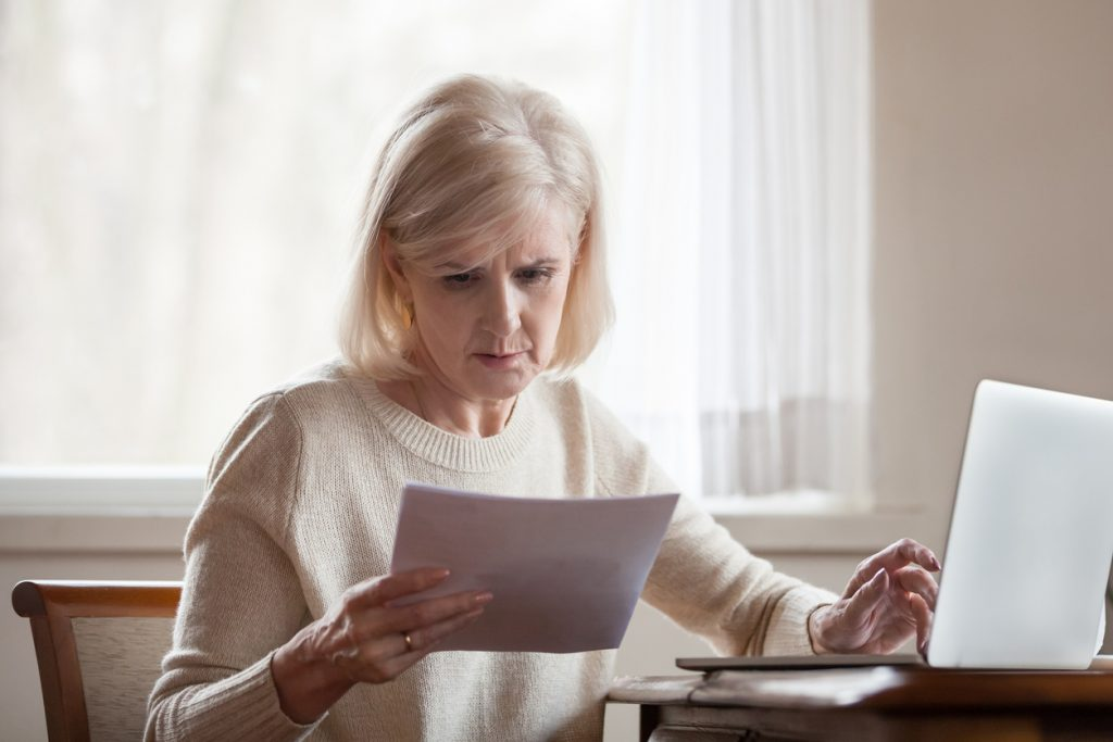 Serious frustrated middle aged senior woman worried reading bad news in paper letter document, stressed upset mature lady troubled with medical bills