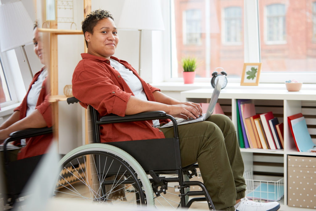 Portrait of African young woman with disabilities sitting in wheelchair and looking at camera while using laptop computer at home