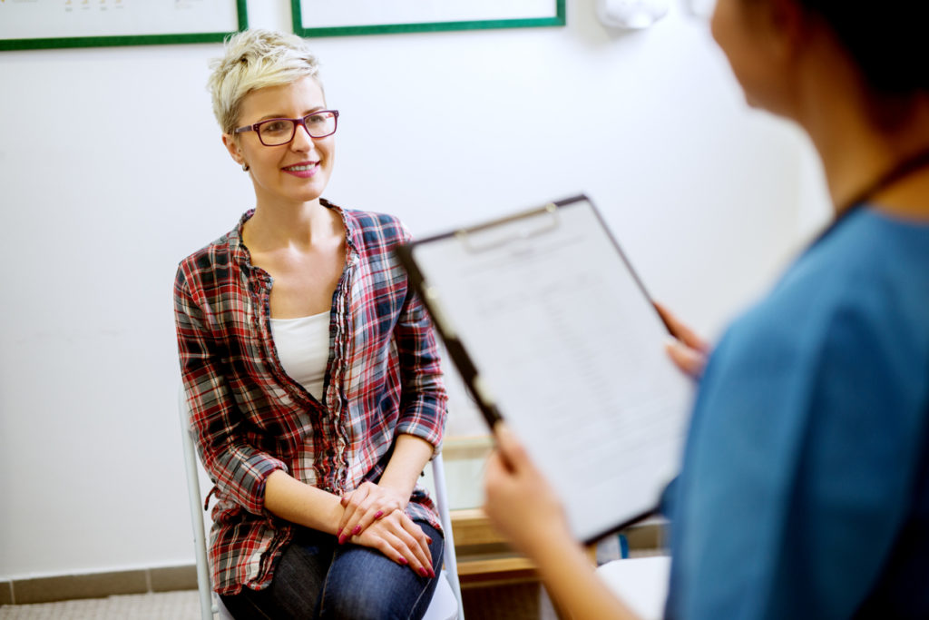 Beautiful happy middle aged short hair woman with eyeglasses sitting in front of a nurse with the clipboard.