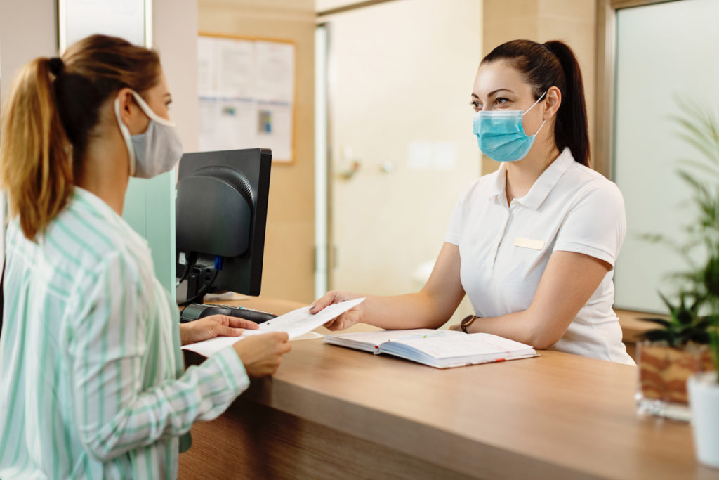 receptionist and her patient wearing face masks