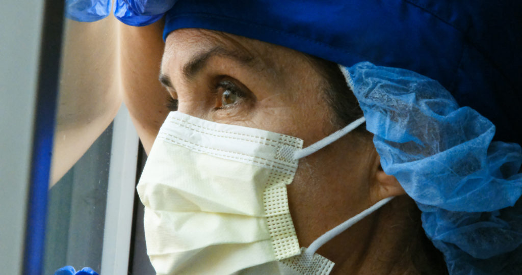 Overworked, female mature health care worker looking through a window