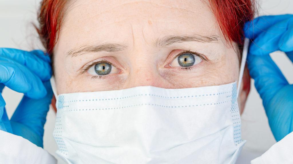 Close-up portrait of a nurse adjusting her protective surgical mask